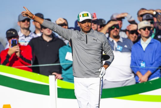Rickie Fowler signals after teeing off on the 15th hole during the first round of the Waste Management Phoenix Open.