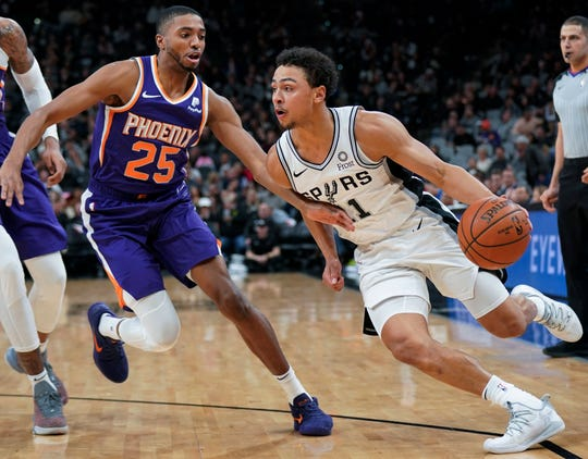 Spurs guard Bryn Forbes tries to drive around Suns forward Mikal Bridges during a game Jan. 29 in San Antonio.
