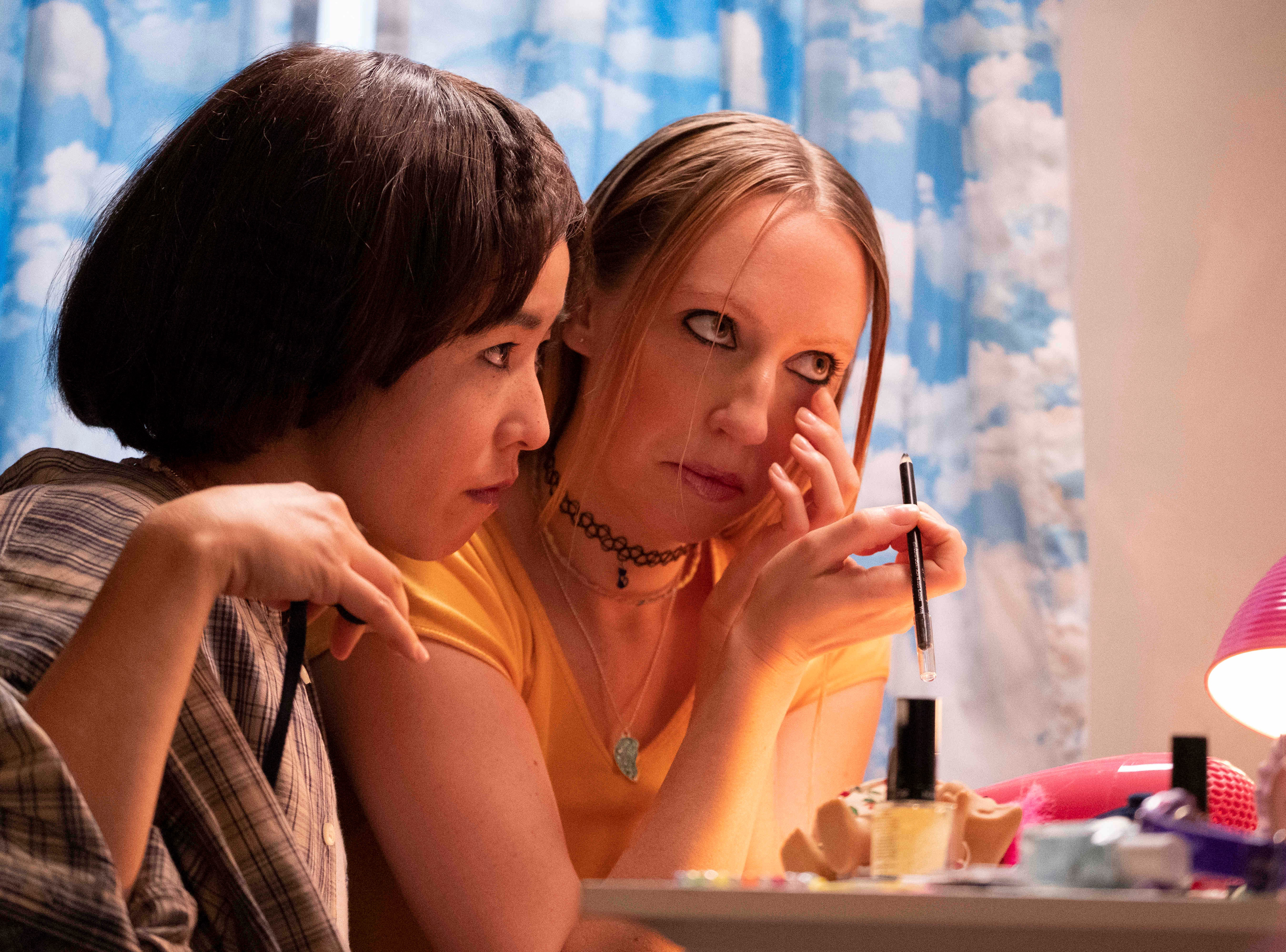 "Maya (Maya Erskine, left) and Anna (Anna Konkle) work on their makeup skills in ""PEN15."""