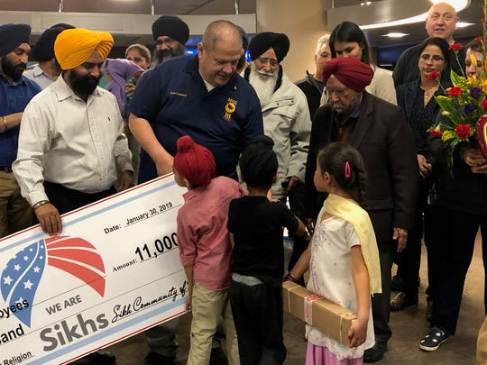 Children of the Phoenix Sikh community give out gas and grocery cards on Wednesday. The Sikh community raised $11,000 to donate to TSA workers affected by the government shutdown.