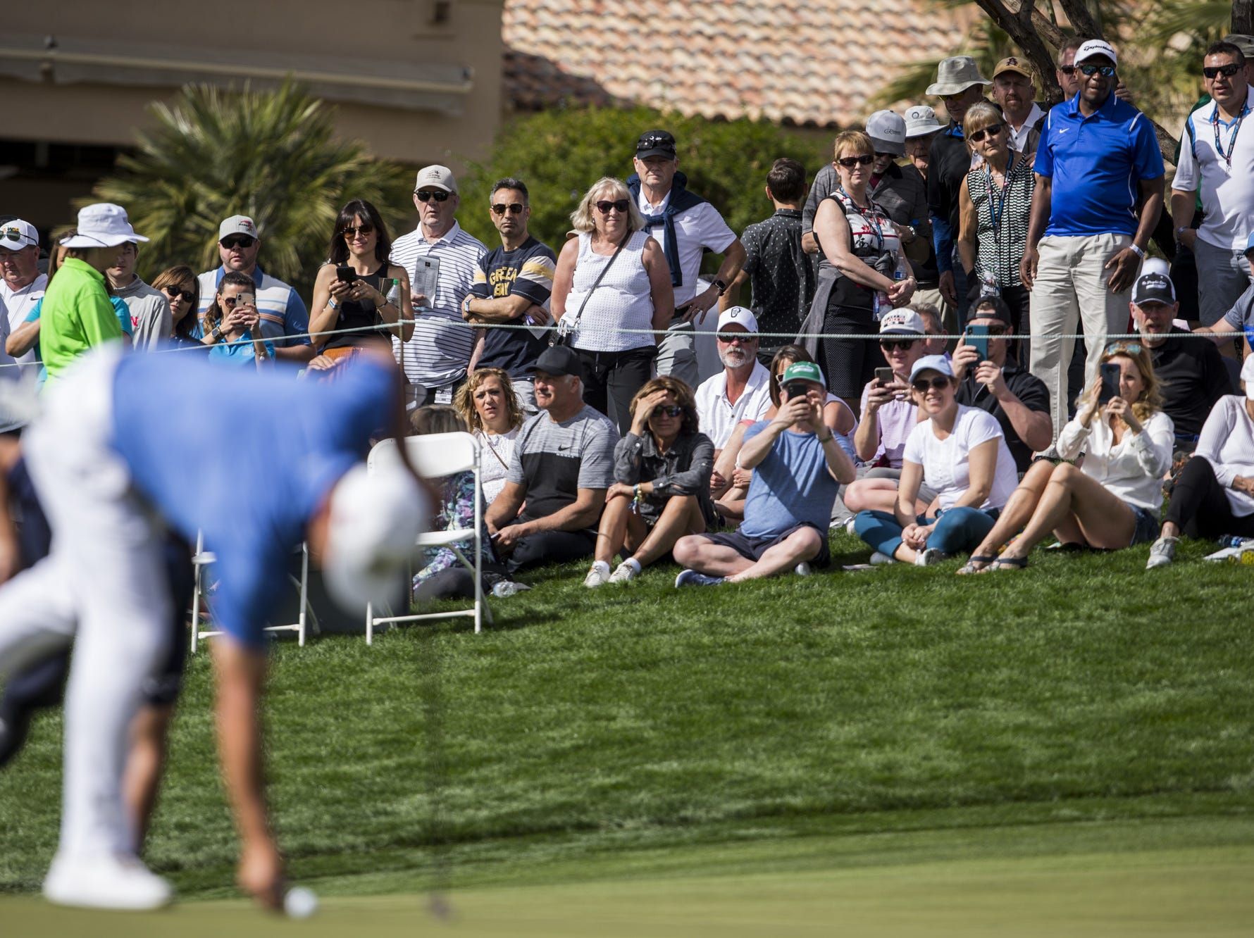 Fans watch as Gary Woodland prepares to putt at the 1st hole during the first round of the Waste Management Phoenix Open.