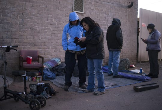 Vicki Helland, center, of Community Bridges, talks with Jimmy Ray Odom (left) while completing a survey during Maricopa County's annual Point-in-Time count of homelessness, January 22, 2019, in an alley near Jackson Street and 1st Avenue in Phoenix. Anne Scott (right, Maricopa Association of Governments) also talks with another person.