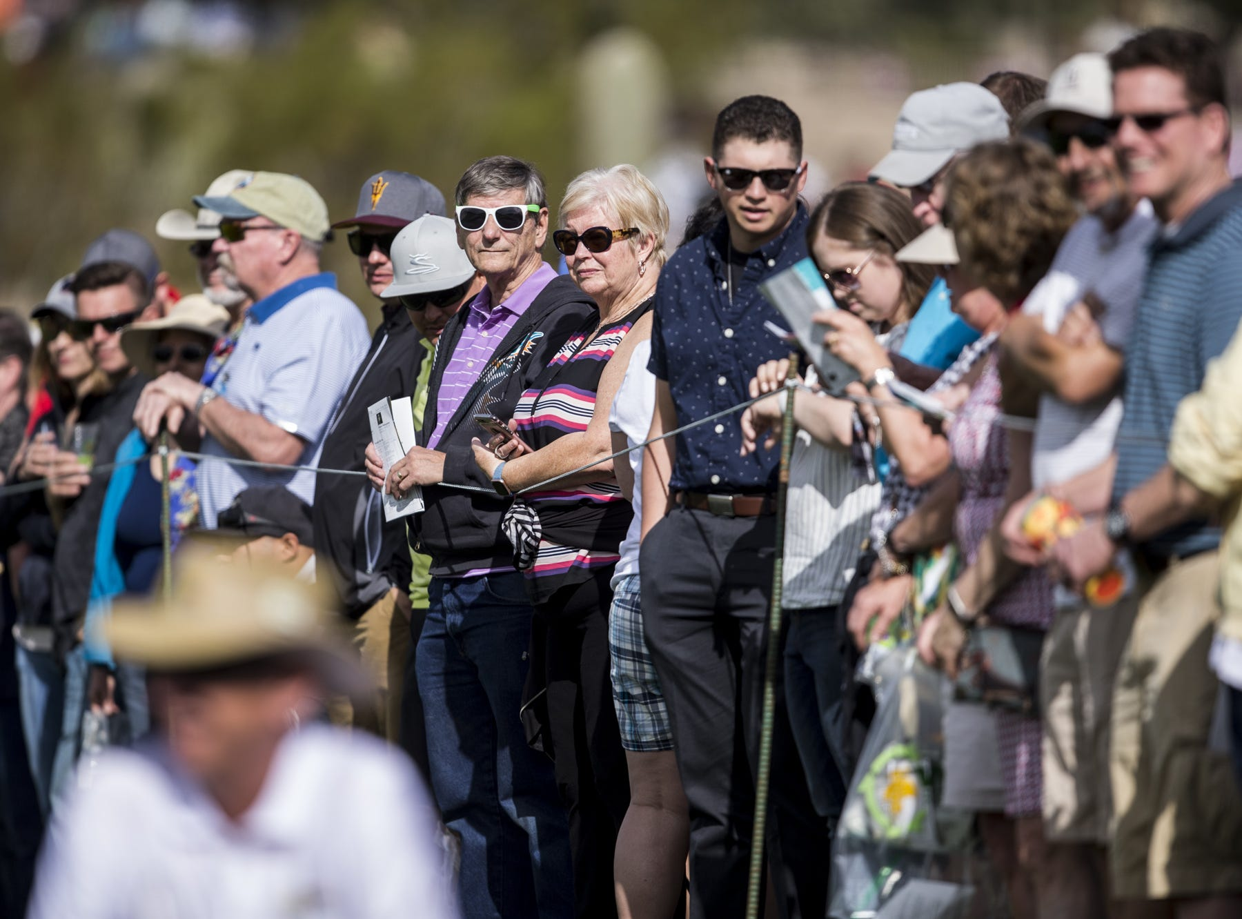 Fans look on from the 1st hole during the first round of the Waste Management Phoenix Open.