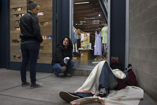 Vicki Helland (center) and Liz DaCosta (left, both of Community Bridges) check on a man during Maricopa County's annual Point-in-Time count of homelessness,  January 22, 2019, in downtown Phoenix.