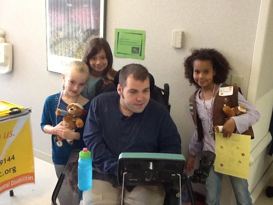 Center, disabilities speaker Joseph Mundt meets with children as part of an event organized by the Arc of St. Clair County. The Arc of St. Clair County is an organization advocating for people with intellectual or developmental disabilities.