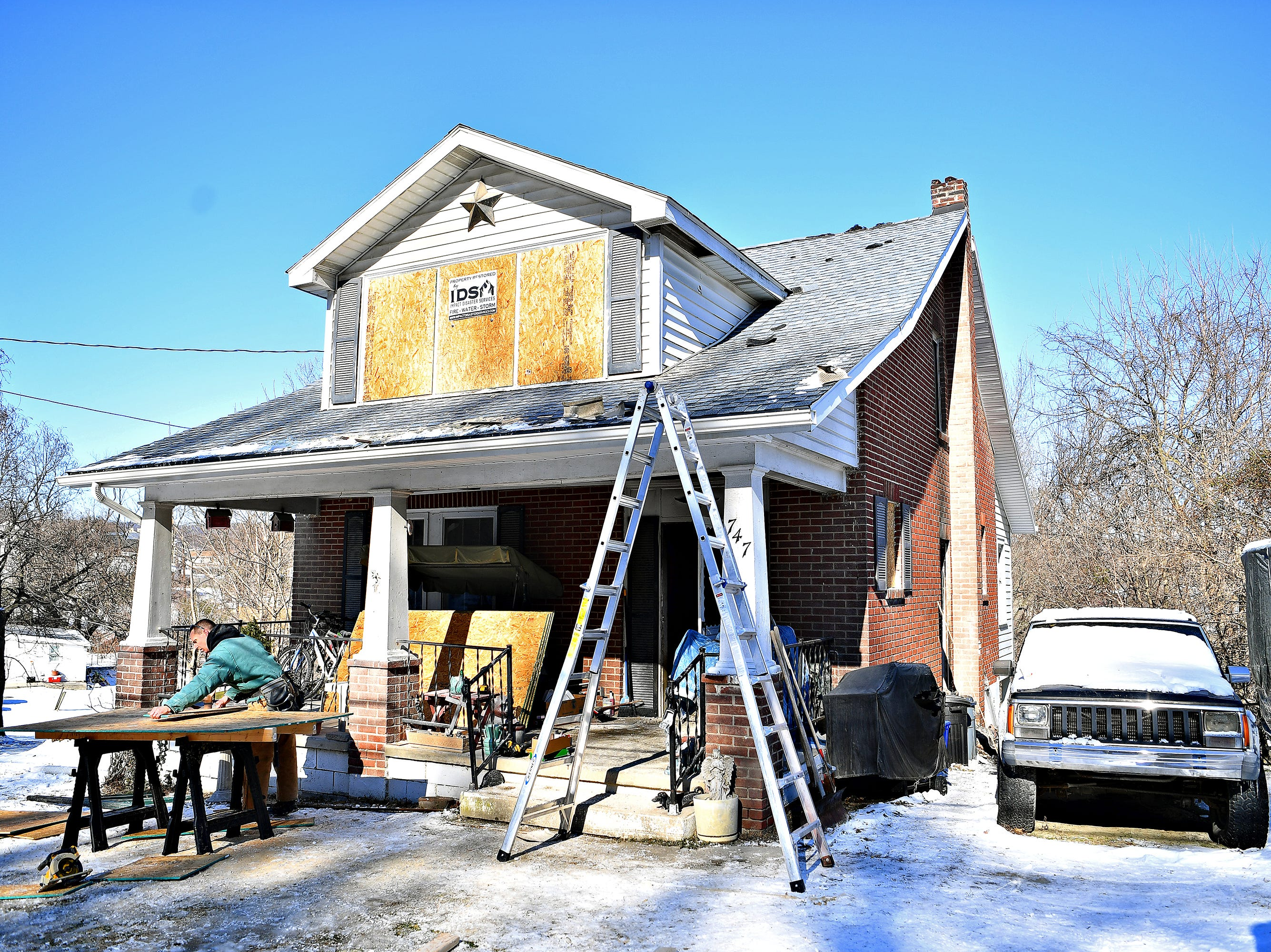 Jeremy Charles, with Impact Disaster Services, cuts boards to cover broken windows to secure a home in the 700 block of South Front Street that was damaged in an early morning fire in Wrightsville, Thursday, Jan. 31, 2019. Dawn J. Sagert photo