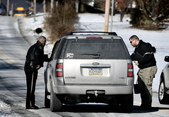 A Northern York County Regional Police officer, left, and a York County Deputy Coroner talk with a motorist on the scene of a fatal accident involving involving a passenger car and a loaded school bus on Lewisberry Road in Conewago Township Thursday, Jan. 31, 2019. No students on the bus were hurt according to police. Bill Kalina photo