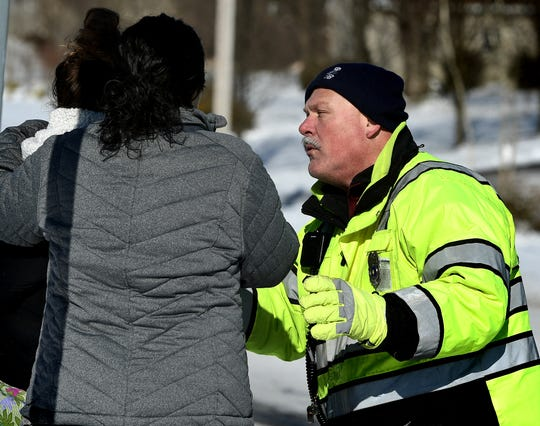 A fire policeman talks with women on the scene of a fatal accident involving involving a passenger car and a loaded school bus on Lewisberry Road in Conewago Township Thursday, Jan. 31, 2019. No students on the bus were hurt according to police. Bill Kalina photo