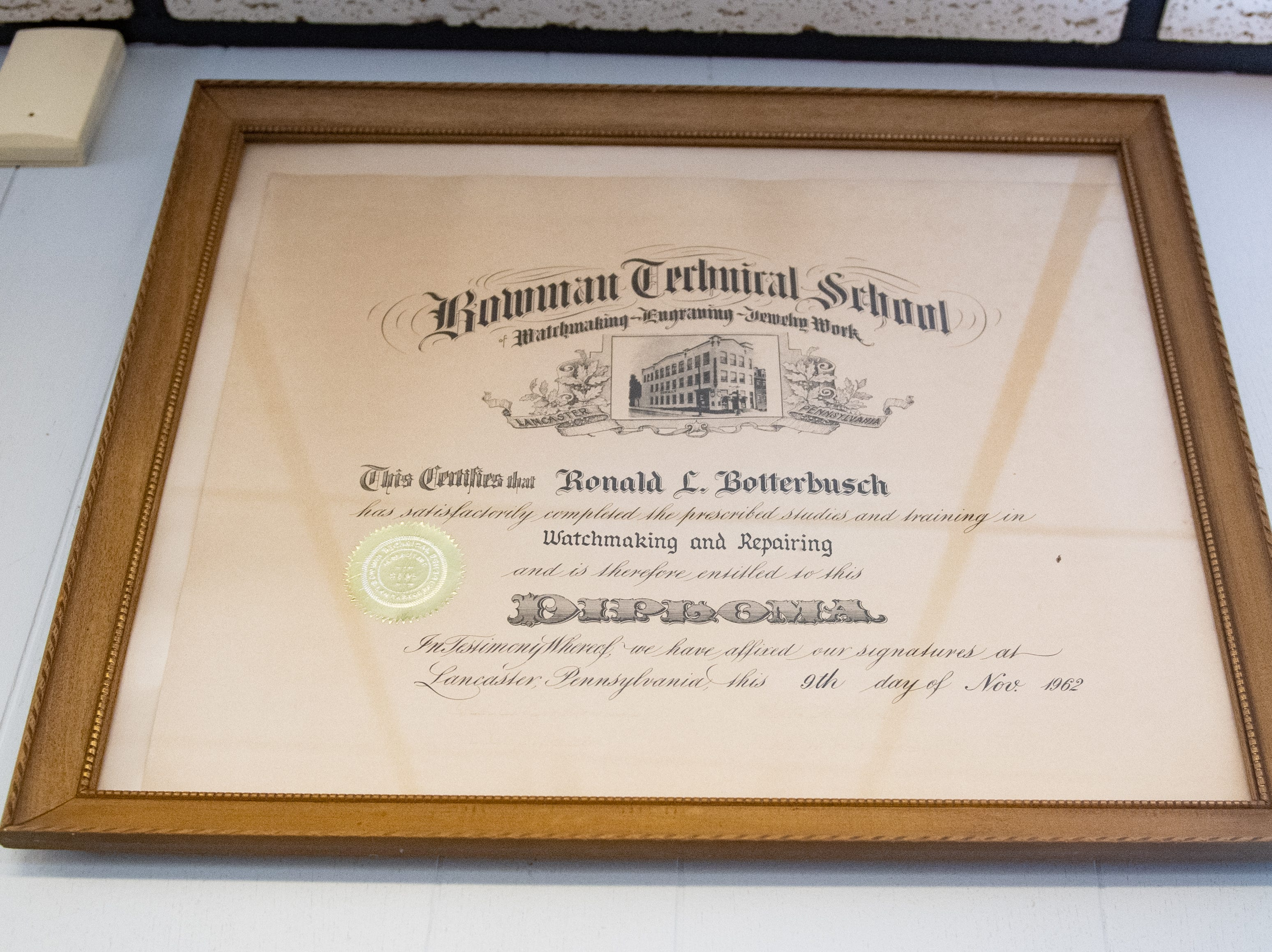 Ronald Botterbusch's watchmaker school diploma hangs in the front of the store, January 30, 2019.