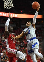 Nevada Wolf Pack guard Jazz Johnson (22) shoots against UNLV Runnin' Rebels forward Cheikh Mbacke Diong (34) during the second half at Thomas & Mack Center.