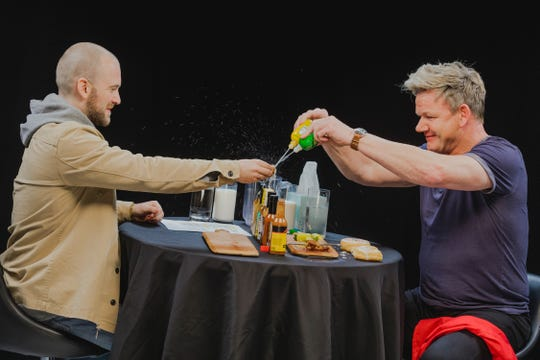 """Gordon Ramsay squirts a wing with lemon and lime juice in an attempt to combat the heat on an episode of """"Hot Ones,"""" hosted by Sean Evans."""