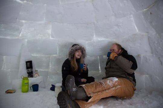 Anika Peterson, 12, enjoys a cup of hot cocoa with her dad, Craig Peterson, inside of an igloo they built together in the backyard of their home in Penfield on Jan. 31, 2019. The igloo is tall enough for Anika to stand up in, and took them about eight hours over the course of several days to build.