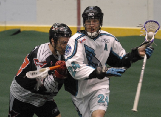 Rochester Knighthawk John Grant (right) moves the ball to the Philadelphia Wings' goal during a game played in 2007.