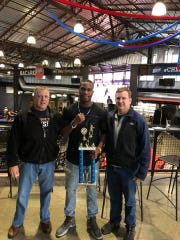 Monroe County Sheriff's Deputy Lawrence King Jr., center, with his 178-pound championship trophy at Golden Gloves tournament in Buffalo last spring. King makes his pro debut Friday at the Main Street Armory.
