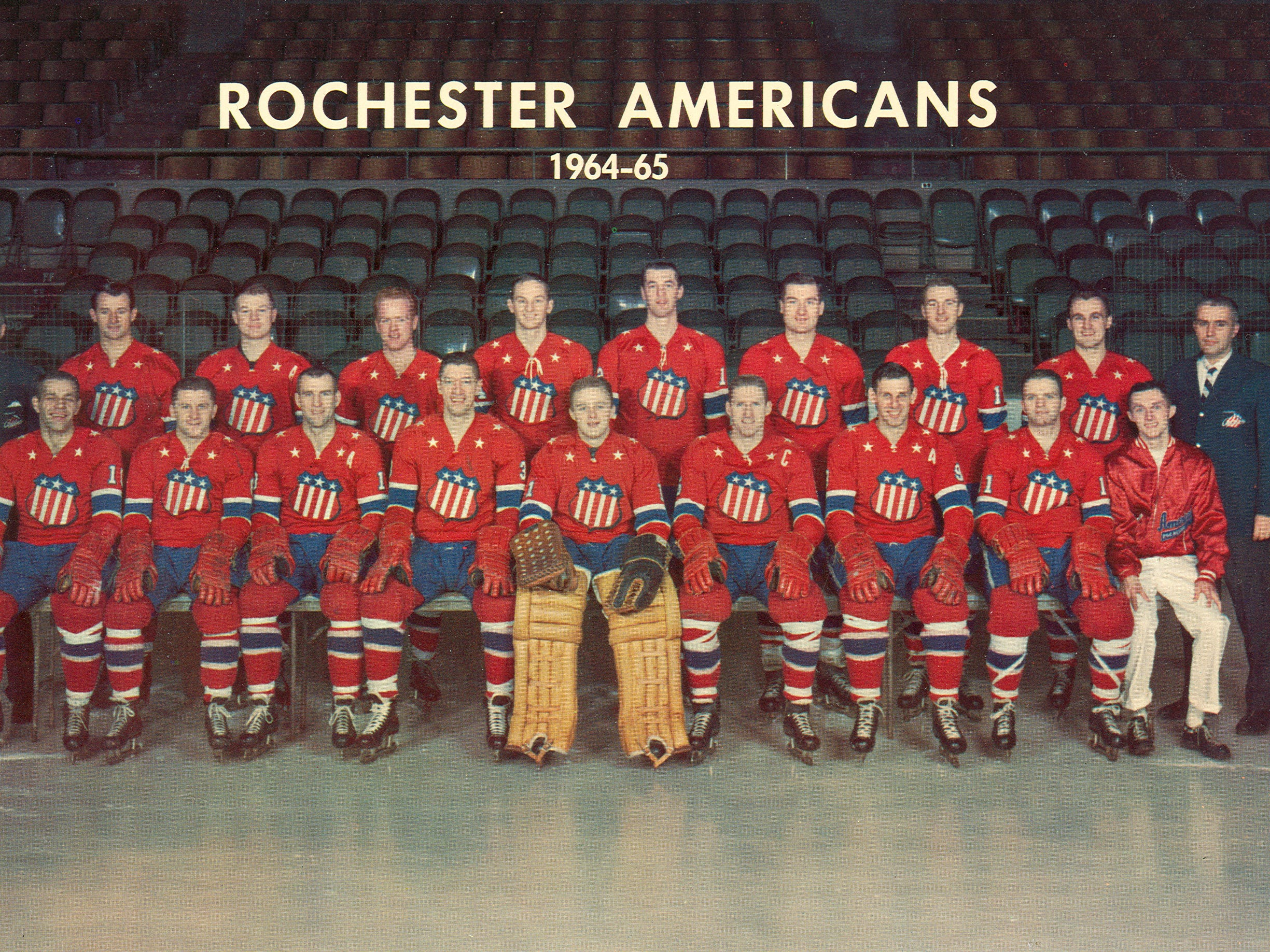 """Joe Crozier, back left, led the Rochester Americans to three Calder Cup championships in his six seasons as coach of the Rochester Americans. The 1964-65 team was the first Calder Cup championship club in team history. Team members included, front row, left to right: Stan Smrke, Wally Boyer, Gerry Ehman, Al Arbour, Gerry Cheevers, Larry Hillman (captain), Dick Gamble (assistant captain) Less Duff, Ken Carson (trainer). Second row: Joe Crozier (coach and GM), Bronco Horvath, Don Cherry (assistant captain), Norm """"Red"""" Armstrong, Jim Pappin, Ed Litzenberger, Duane Rupp, Don McKenney, Darryl Sly, Dave Faunce (publicity director)."""