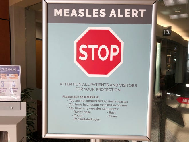 Signs posted at The Vancouver Clinic in Vancouver, Wash., warn patients and visitors of a measles outbreak on Wednesday, Jan. 30, 2019. The outbreak has sickened more than 50 people in the Pacific Northwest.