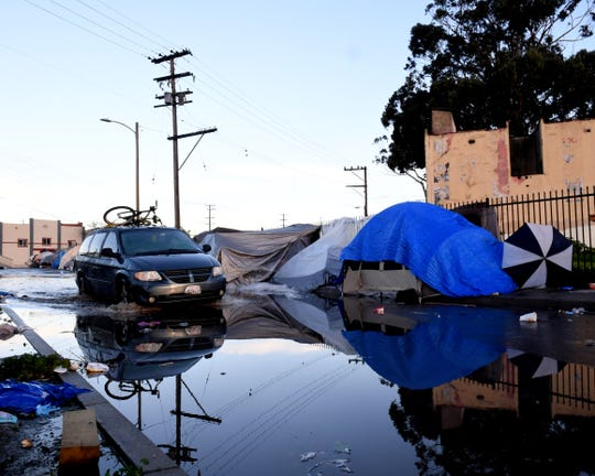 A van drives through a flooded Market Way in Salinas' Chinatown neighborhood.