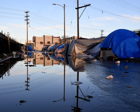 Tents along a flooded Market Way in Salinas' Chinatown.