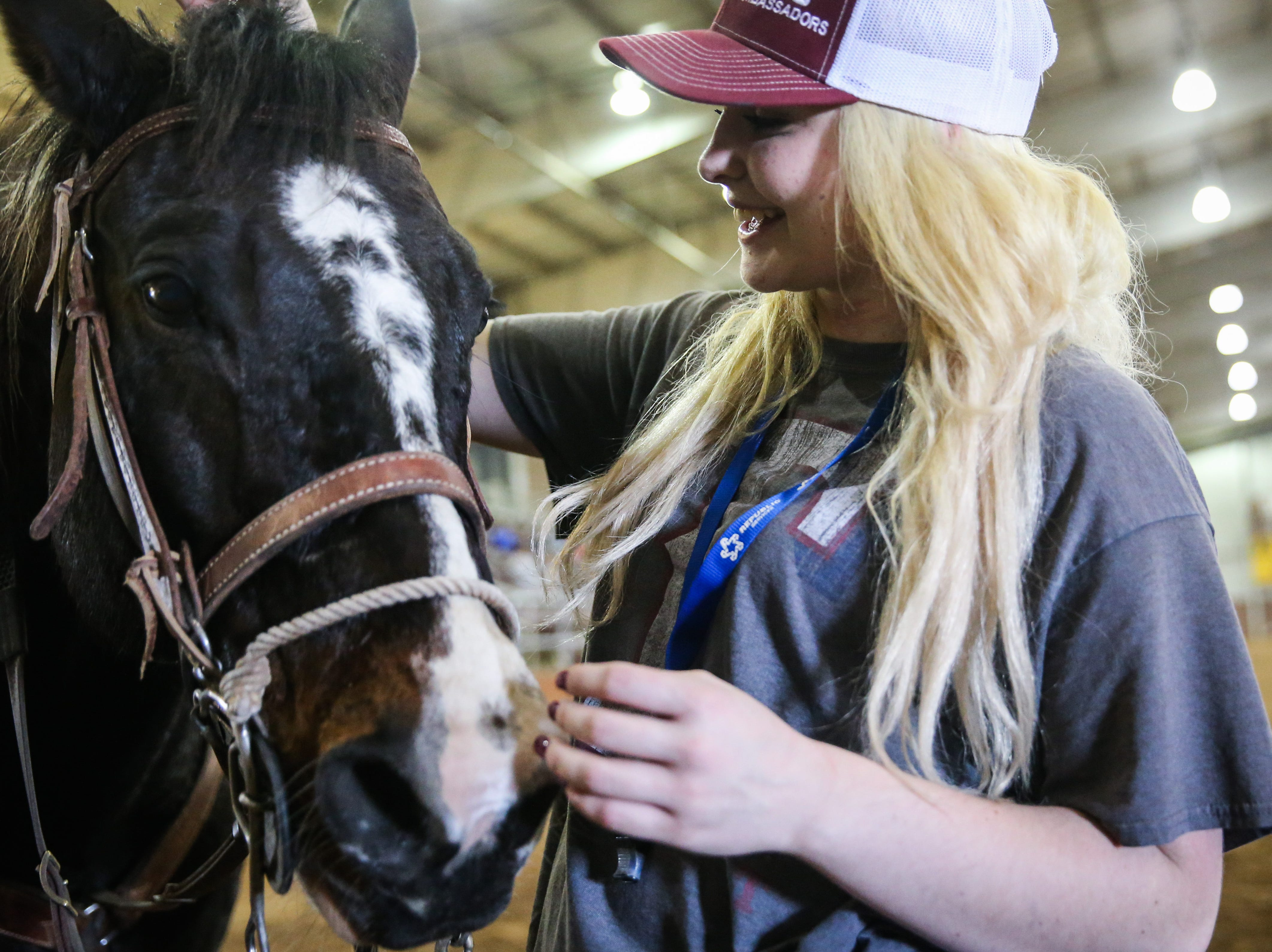 Lauren Feller pets her horse, Cruz, during practice with the San Angelo Ambassadors Saturday, Jan. 26, 2019, in the Spur Arena. The team performs during the San Angelo Stock Show and Rodeo.
