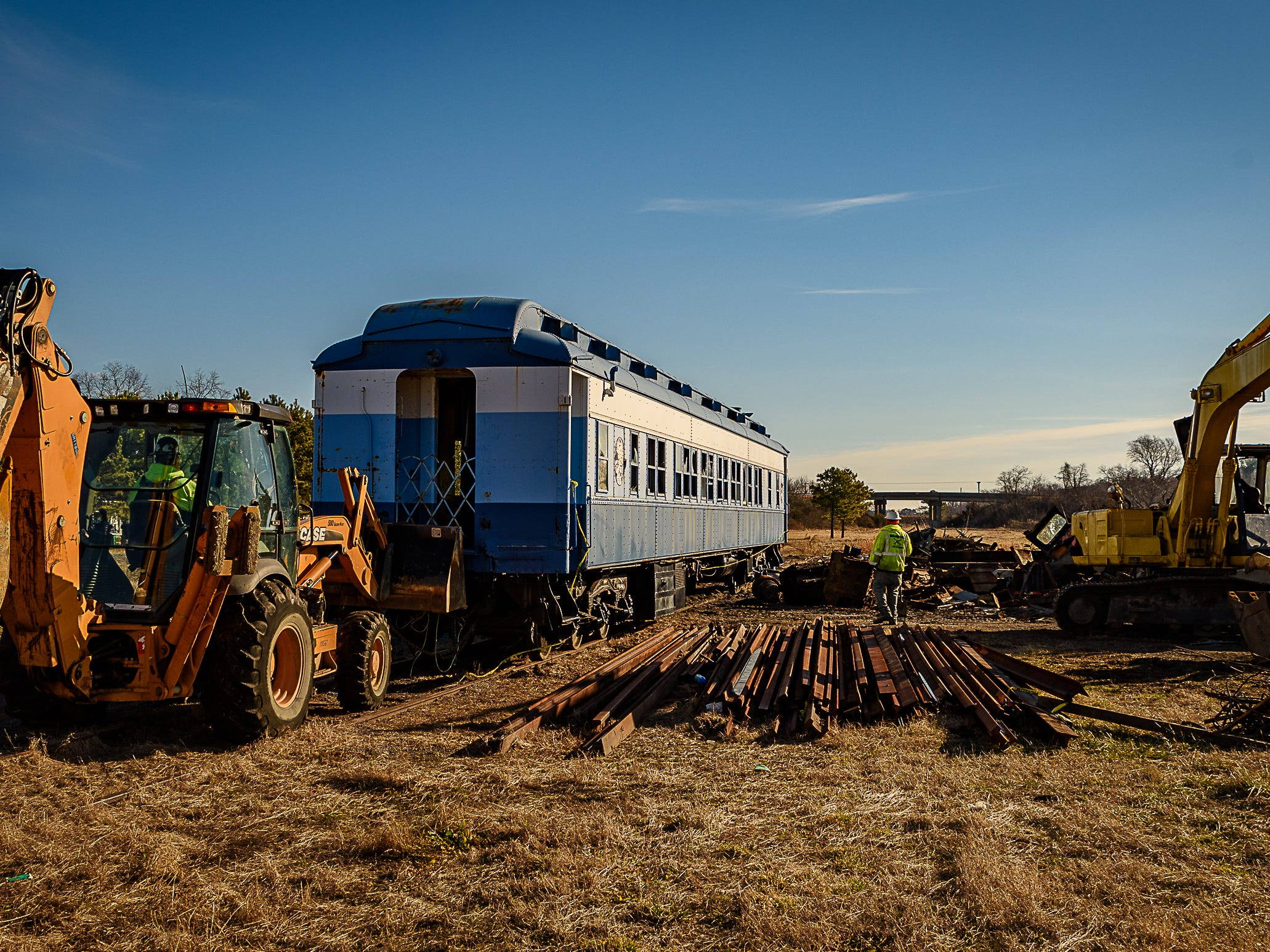The railway car is pushed past the remains of a Bay Coast engine and salvaged rails.