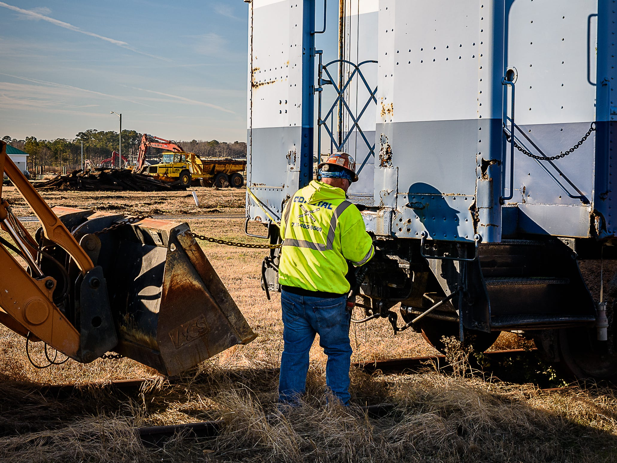 A worker begins hooking equipment to start the process of moving a railway car in Cape Charles.