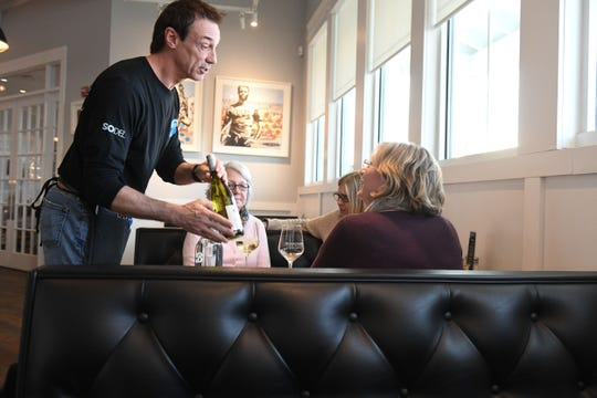 Eric Overman, a server at  Bluecoast restaurant in Rehoboth Beach, serves a bottle of wine to guests on Wednesday, Jan. 30, 2019.