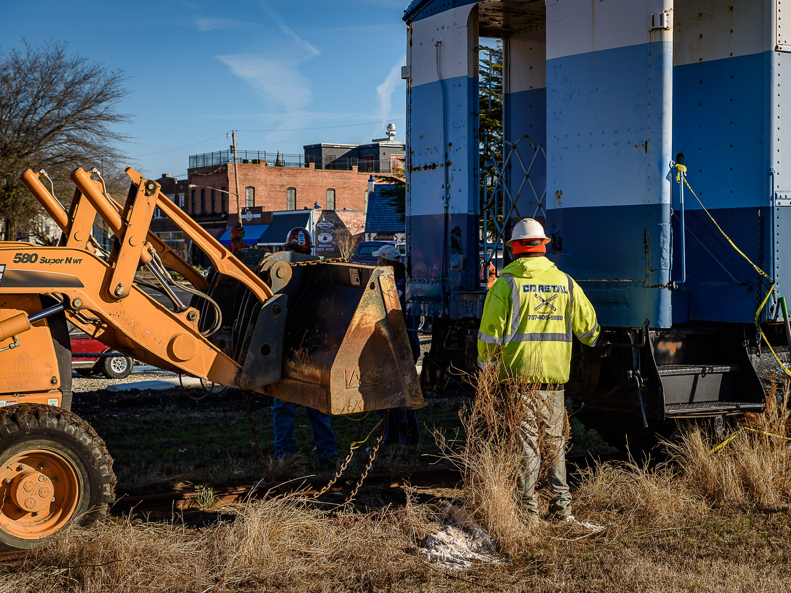 Once separated, an earthmover is used to push the railway car to its new location in Cape Charles.