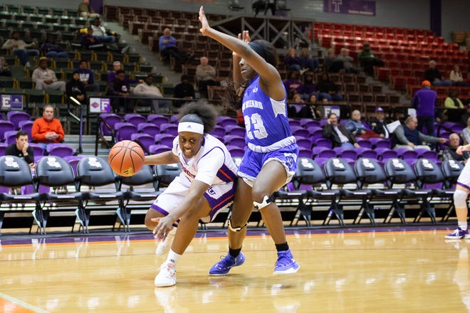 NSU's Nautica Grant drives past UNO's Dionjhae Thomas on Wednesday.