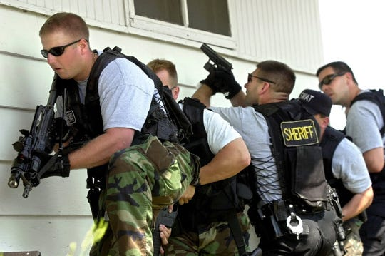 File: Jason Gearman (left) leads the Minnehaha County Sheriff's Department SWAT team as members get ready to enter an abandoned house during training exercises in Sioux Falls. Team members say the drills prepare them for real emergencies.