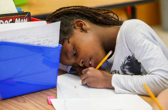 Kunique Calip, a third grade student at Weller Elementary School, works on a haiku during class on Thursday, Jan. 31, 2019.