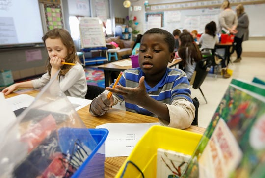 Michael Changa, right, a third grade student at Weller Elementary School, counts the syllables while working on a haiku during class on Thursday, Jan. 31, 2019.