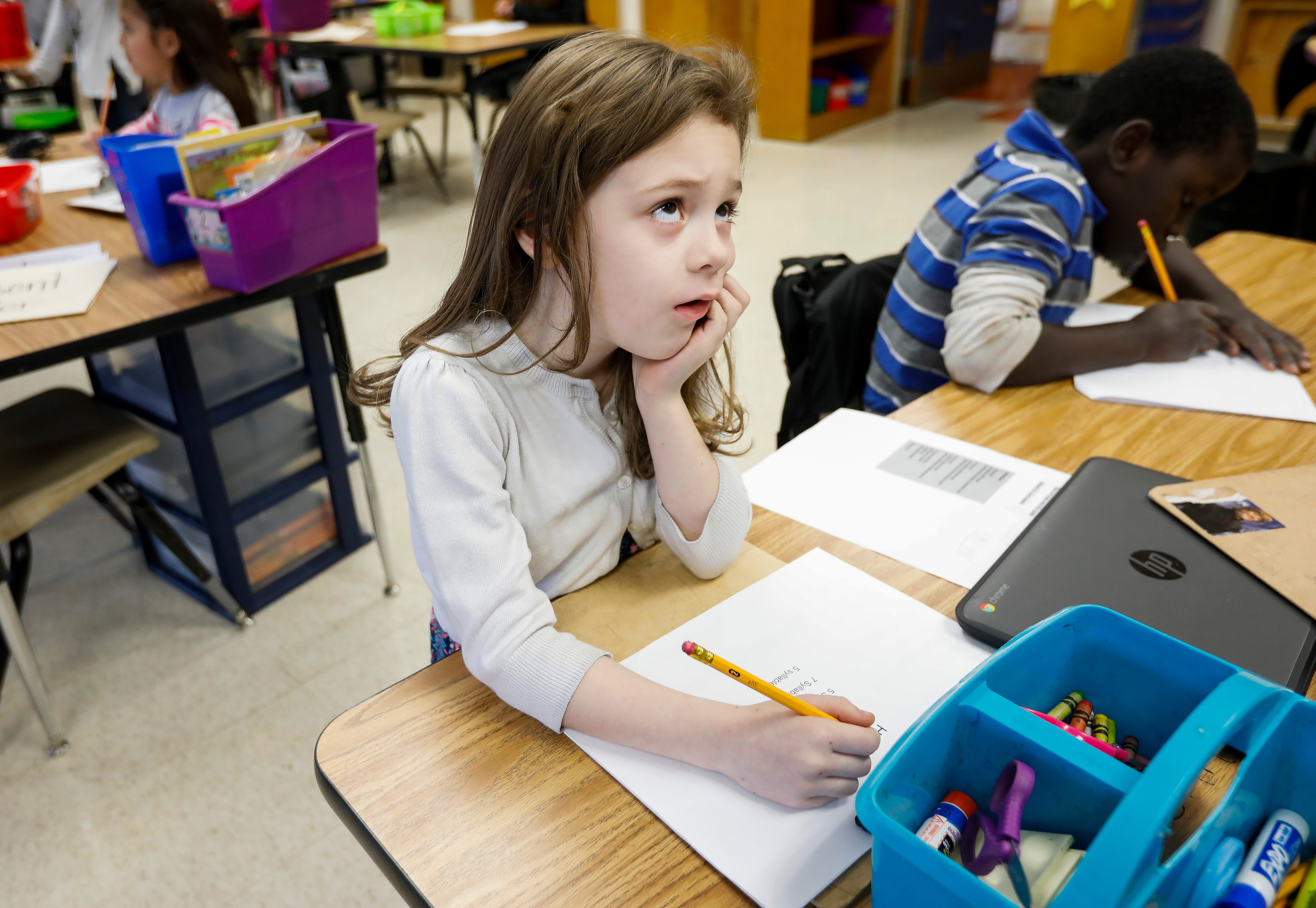 Kaitlyn Stoops, a third grade student at Weller Elementary School, concentrates on coming up with the beginning of her haiku during class on Thursday, Jan. 31, 2019.