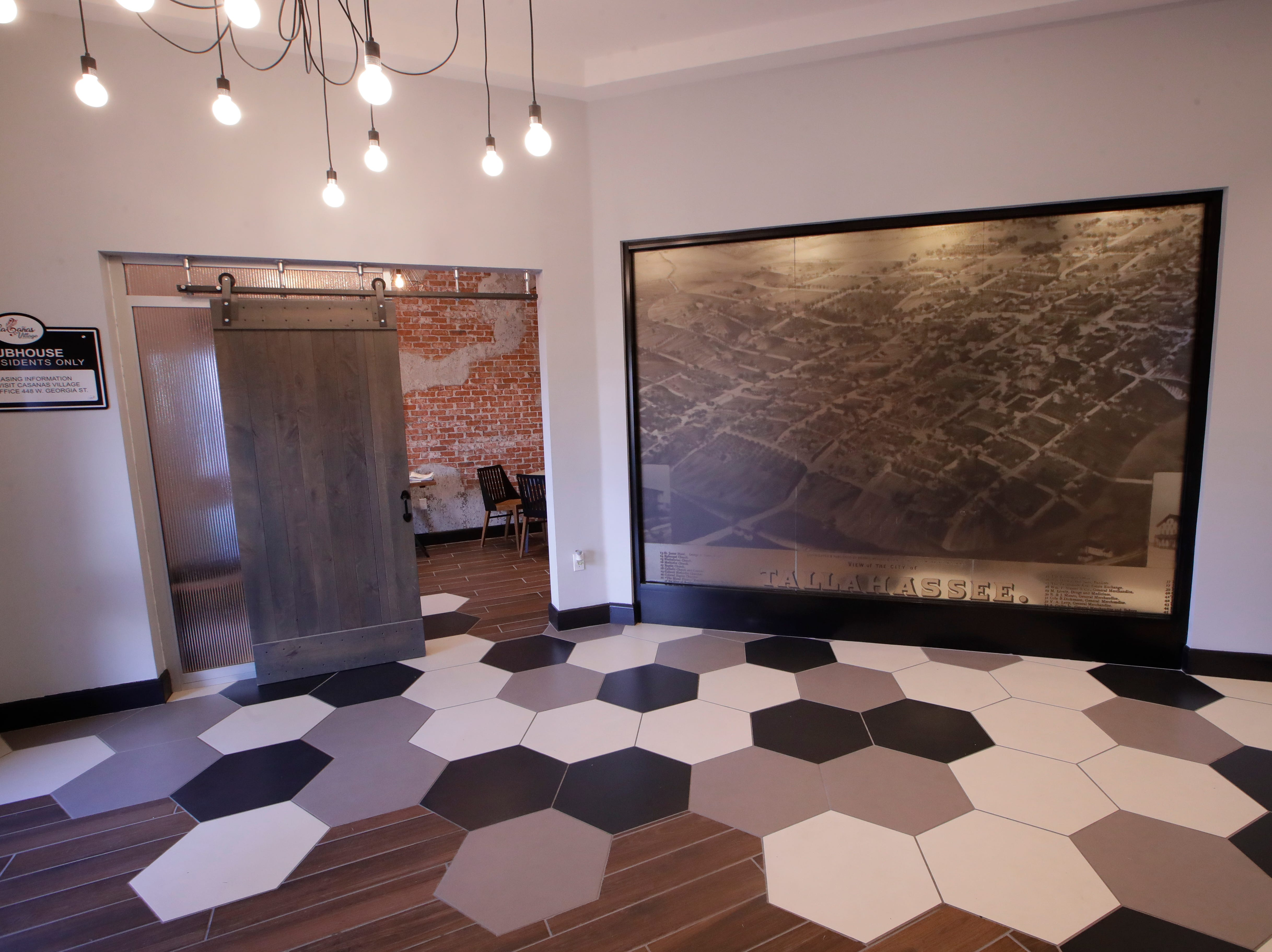 The entrance to Casañas Village Apartments at Frenchtown Square includes a vintage photo of Tallahassee and tile floors leading to a community room.