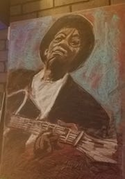 One of Jabare's blues artist paintings on the wall at Blue Tavern.