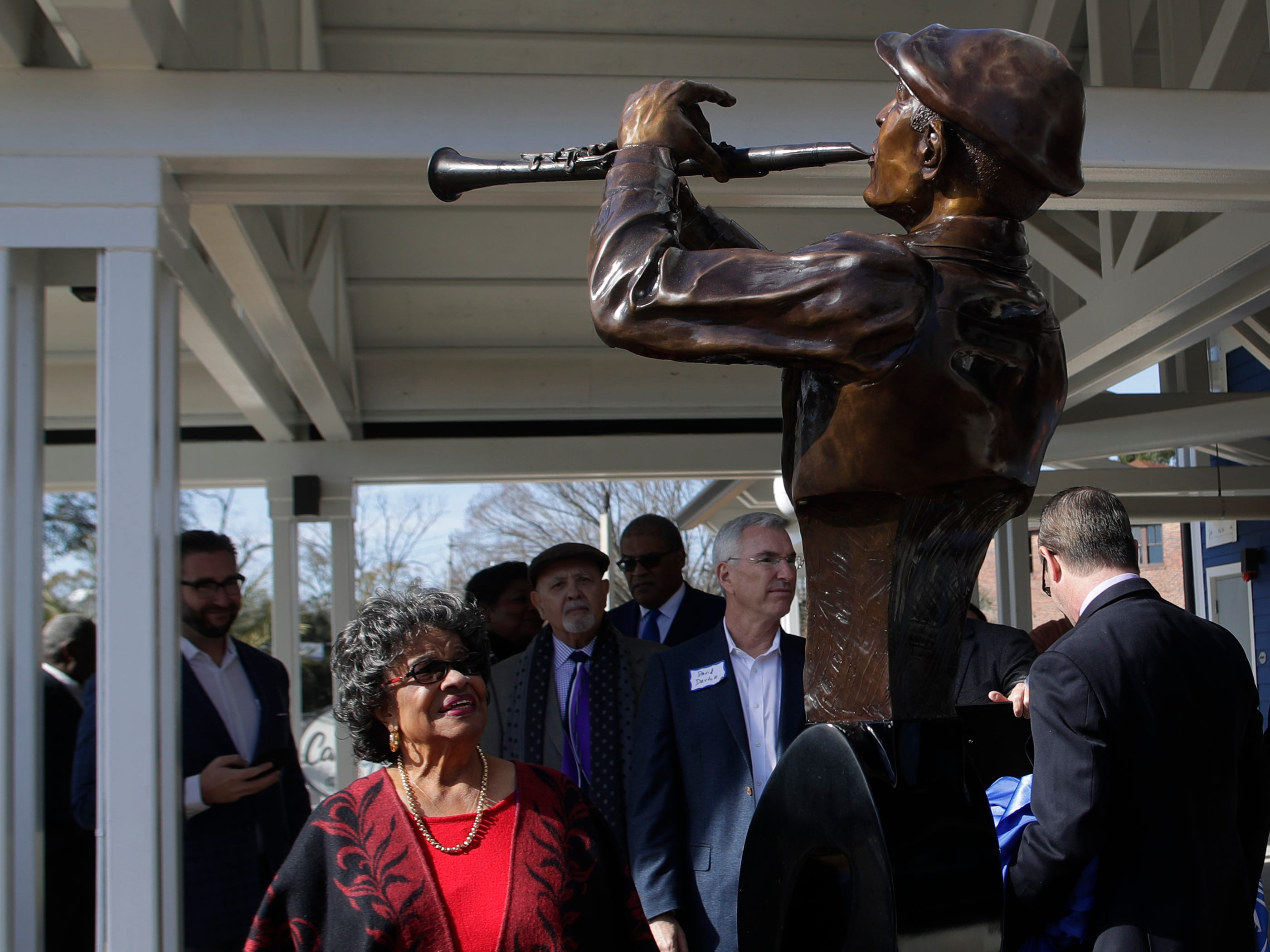 """Lucille Casañas Alexander smiles as the statue of her father Aurelío Angel Casañas is revealed at the grand opening celebration for the  Casañas Village Apartments at Frenchtown Square Thursday, Jan. 31, 2019. Casañas came to Tallahassee from Cuba in the late 1800s. The statue portrays him playing the clarinet, which he played in a local group called """"The Tallahassee Band."""""""
