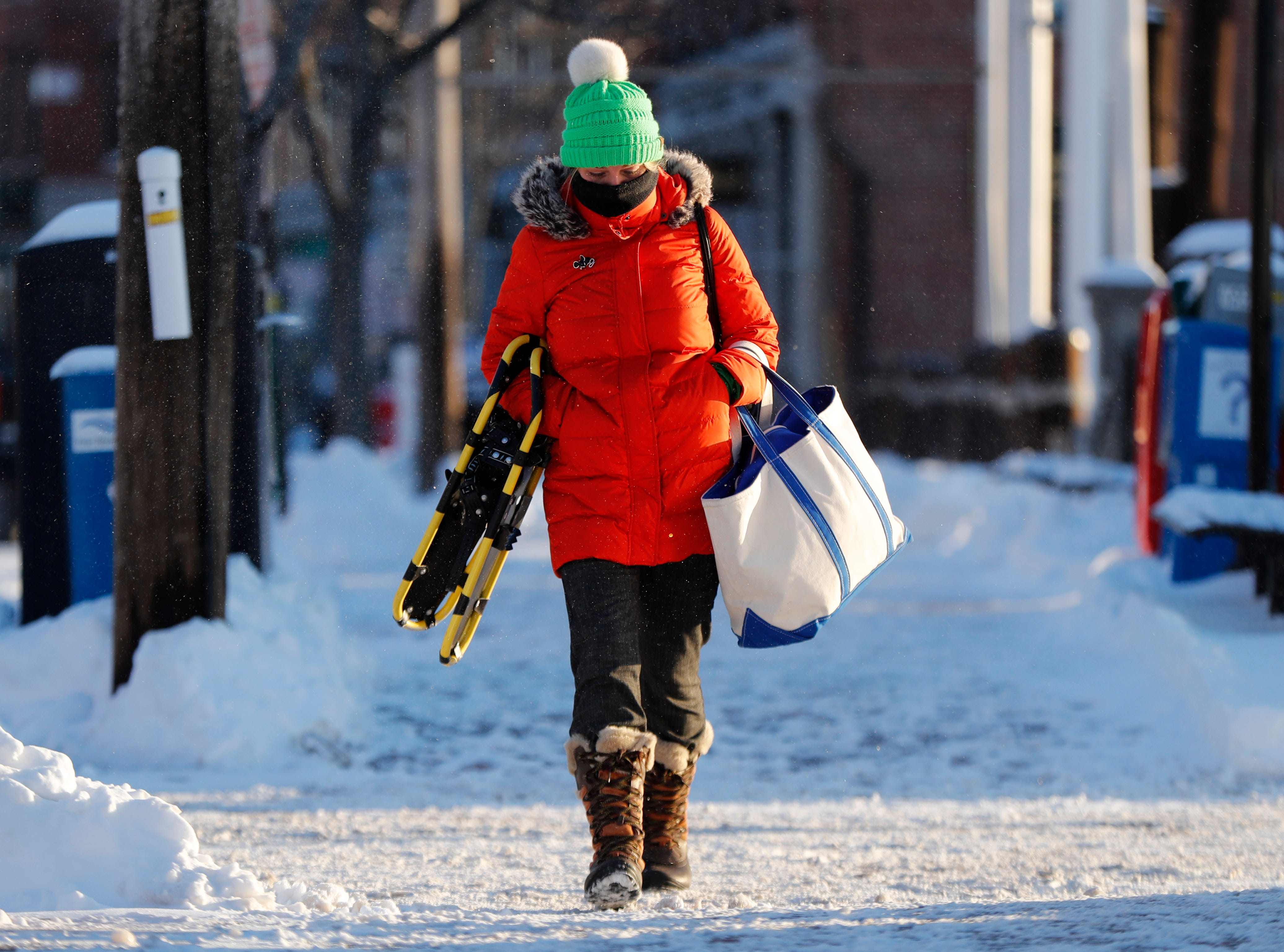Lauren Webster is bundled up as she makes her way to work on a bitter cold morning, Thursday, Jan. 31, 2019, in Portland, Maine, Undaunted by the polar vortex that's making an appearance in northern New England, Webster carries a set of snowshoes that she intends to use at a nearby park after work.