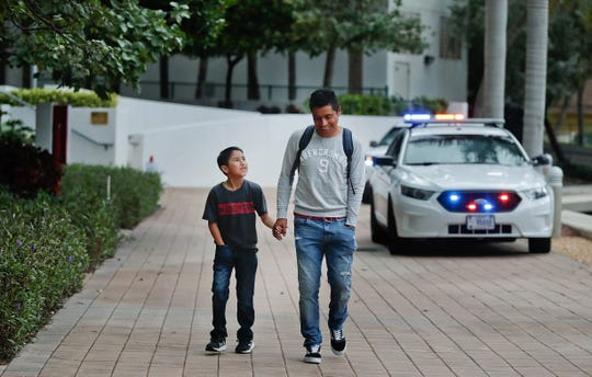 Mynor Diaz-Berduo, 29, of Guatemala, walks down a path with his 10-year-old son (name withheld) outside of the immigration courthouse after court hearings were canceled on Thursday, Jan. 31, 2019, in Miami. U.S. immigration officials blame the government shutdown and the extreme winter weather for confusion about immigration court hearings. In an emailed statement, the part of the Justice Department overseeing immigration courts said some immigrants with notices to appear Thursday wouldn't be able to proceed with those hearings.