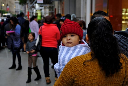 A woman holds a child in a line snaking around the block outside a U.S. immigration office with numerous courtrooms Thursday, Jan. 31, 2019, in San Francisco. The crowd was mixed with people who had court appointments for Thursday, people whose appointments were swallowed up by shutdown and others who had 'Notices to Appear' but assumed that meant they had court dates.