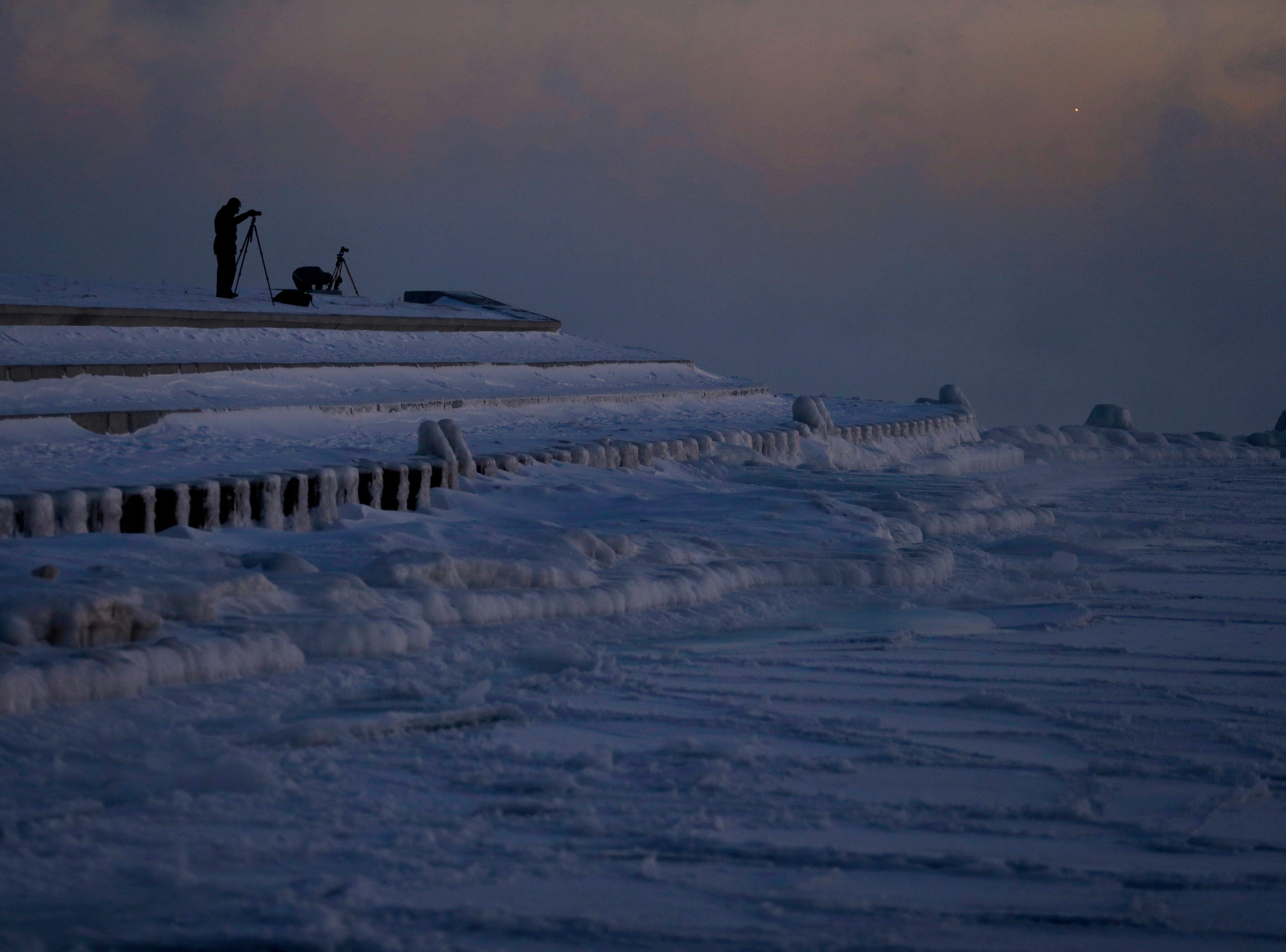 Photographers set up tripods along the shore of Lake Michigan before sunrise, Thursday, Jan. 31, 2019, in Chicago. The painfully cold weather system that put much of the Midwest into a historic deep freeze was expected to ease Thursday, though temperatures still tumbled to record lows in some places.