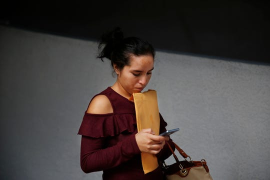 Dania Rivas, 20, of Honduras, clutches an envelope while looking at her phone outside of immigration court after court hearings were canceled on Thursday, Jan. 31, 2019, in Miami. U.S. immigration officials blame the government shutdown and the extreme winter weather for confusion about immigration court hearings. In an emailed statement, the part of the Justice Department overseeing immigration courts said some immigrants with notices to appear Thursday wouldn't be able to proceed with those hearings.