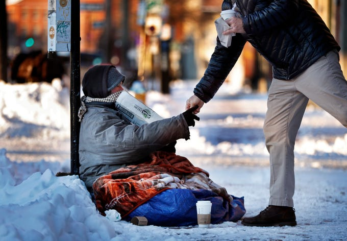 A homeless man sitting outside a coffee shop accepts cash from a customer on a bitter cold morning, Thursday, Jan. 31, 2019, in Portland, Maine, The polar vortex that's bringing misery to the upper Midwest is making an appearance in northern New England, where some places will struggle to reach the single digits.