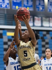 Treasure Coast's Jessica Nerestant (right) goes over Sebastian River's Yasmine Cumming to score two points during the third period of the high school girls basketball game Wednesday, Jan. 30, 2019, at Sebastian River High School.