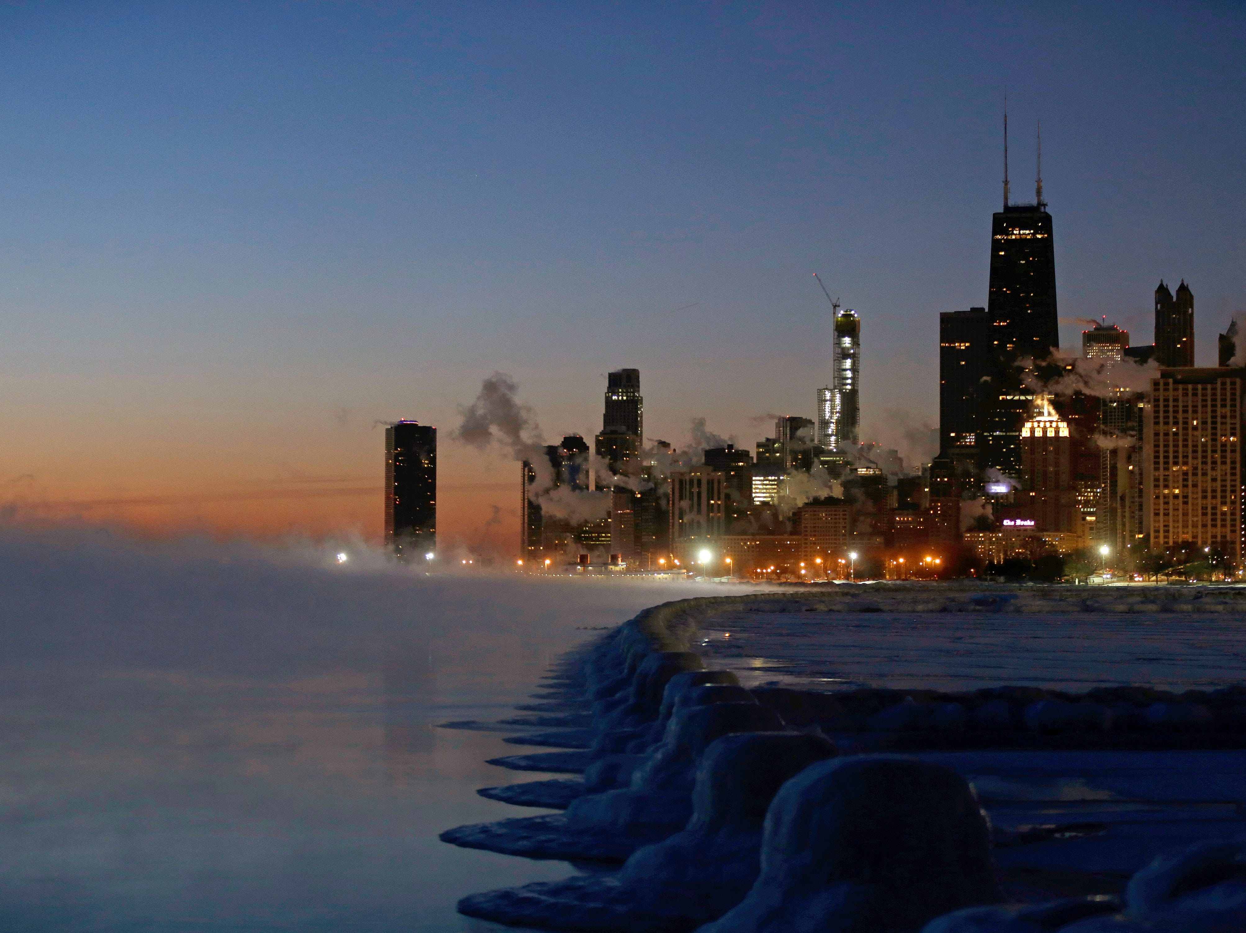Ice forms along the shore of Lake Michigan before sunrise, Thursday, Jan. 31, 2019, in Chicago. The painfully cold weather system that put much of the Midwest into a historic deep freeze was expected to ease Thursday, though temperatures still tumbled to record lows in some places.