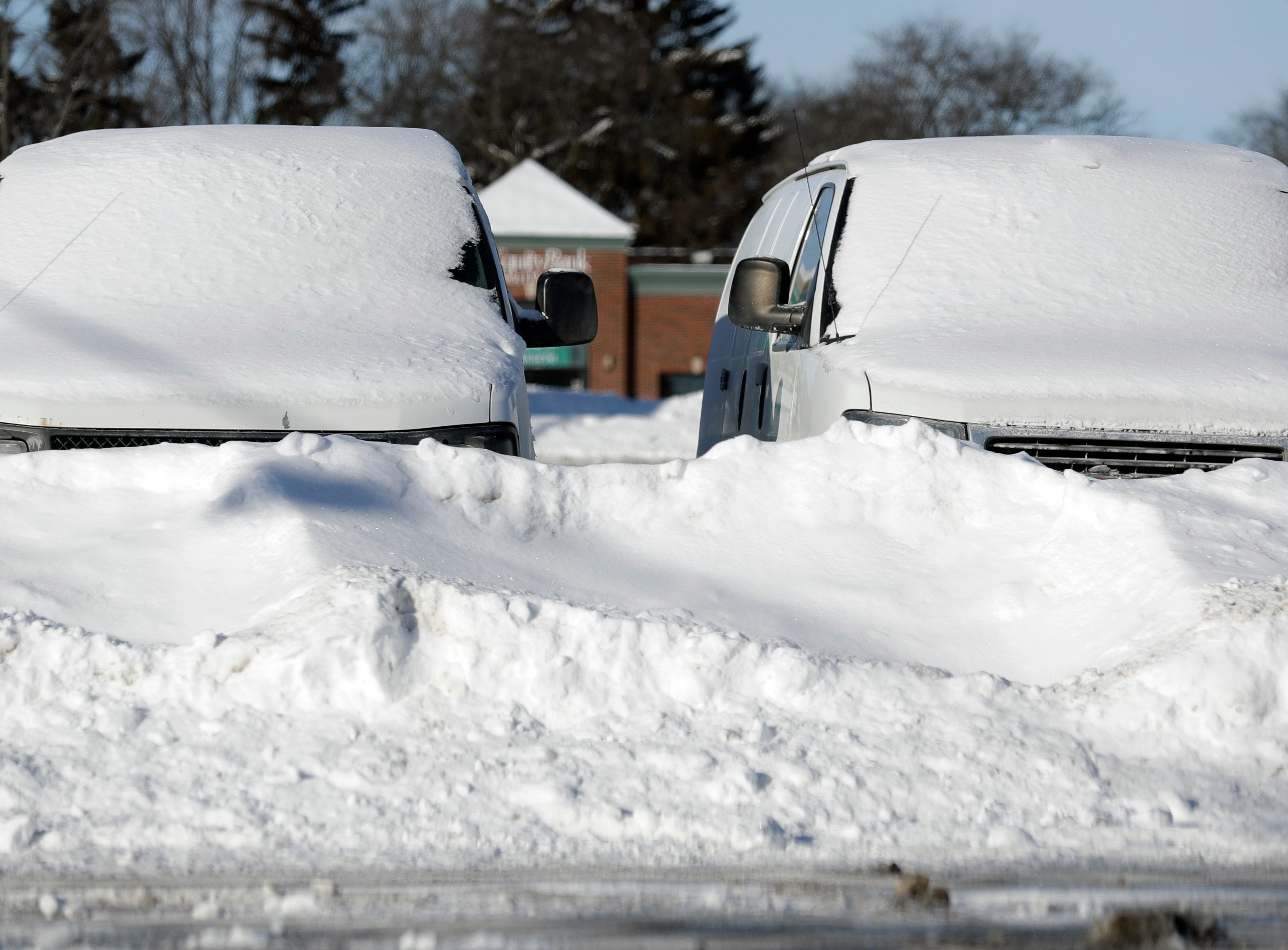 Cars are covered by snow in Buffalo Grove, Ill., Thursday, Jan. 31, 2019. The painfully cold weather system that put much of the Midwest into a historic deep freeze was expected to ease Thursday, though temperatures still tumbled to record lows in some places.