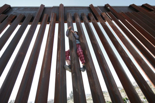 The U.S. Border Patrol and ICE trained recently along the border fence in Anapra. The training was preparation for any border surge that might occur. Here, a child from the Mexican side climbs the border barrier.