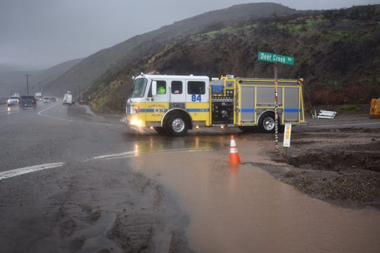 A Ventura County Fire Department engine stages near Deer Creek Road and Pacific Coast Highway, where mud flows closed lanes Thursday.