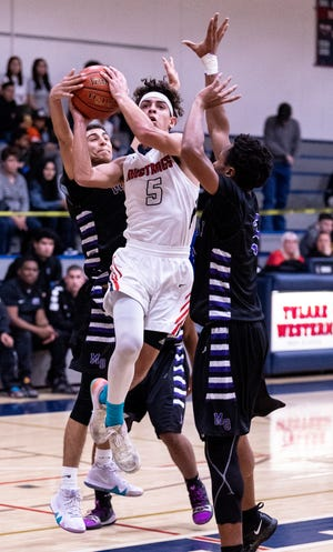 Tulare Western's Mikey Ficher shoots between Mission Oak's Edward Salinas, left, and Anthony Velasquez in boys basketball on Wednesday, January 30, 2019.