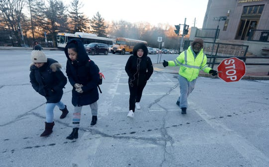 Crossing guard Wesley Dunkley crosses students on their way to school in Ossining Jan. 31, 2019. Despite temperatures hovering in the low single digits, Ossining schools operated on a normal schedule.