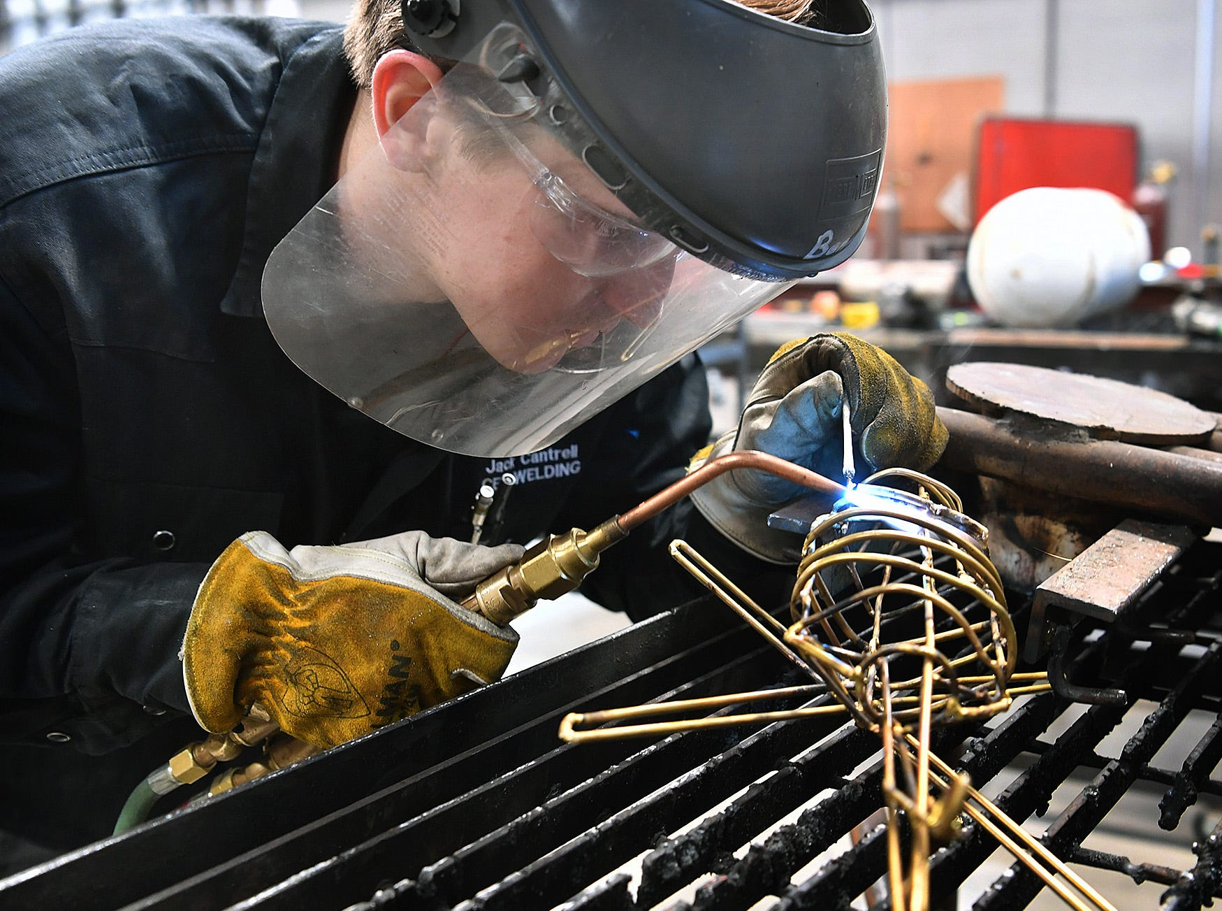 Jack Cantrell, a welding student at the Career Education Center, brazes brass rods together as he creates a sculpture of a Blackhawk helicopter to honor his late brother, Stephen Cantrell, a Blackhawk helicopter pilot who died in a training accident in 2017.