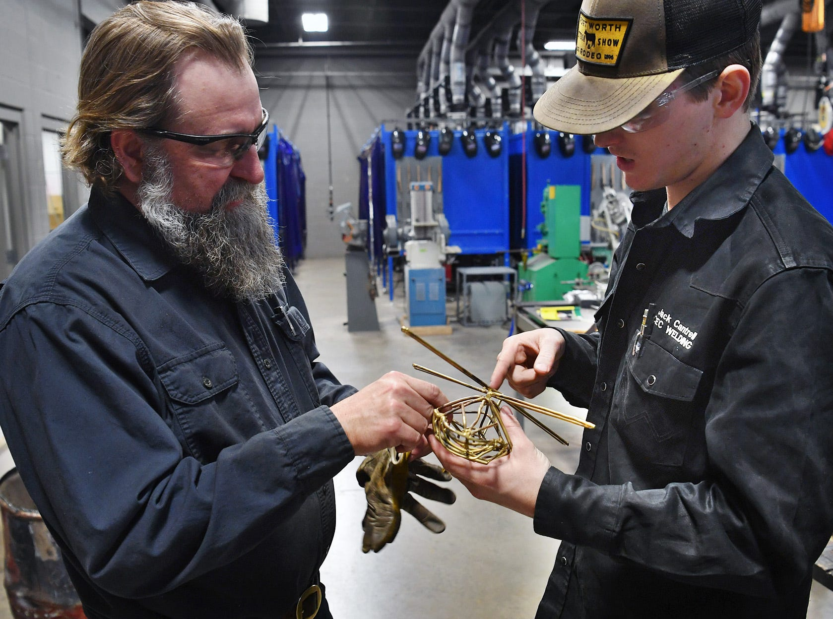 Welding Technology instructor BC Gilbert advises his student, Jack Cantrell, on Cantrell's Skills USA competiton entry, a sculptural replica of a Blackhawk helicopter like the one his brother flew.